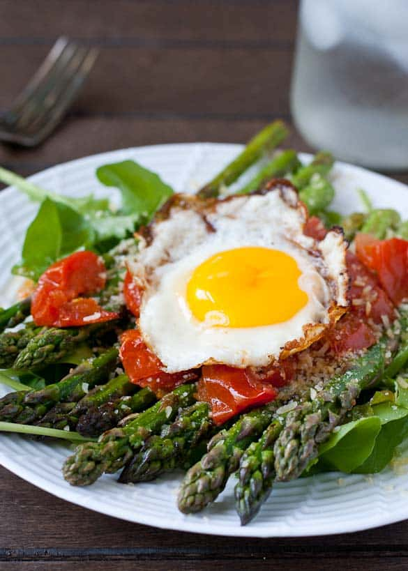 This Warm Asparagus and Tomato Salad is dressed simply with the rich yolk of a fried egg.