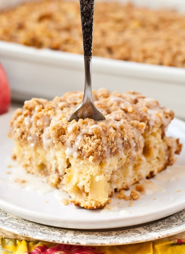 closeup image of a fork in a slice of apple crumb cake topped with icing