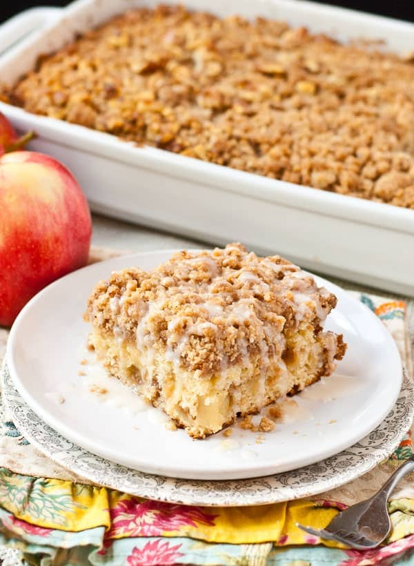 a single slice of apple crumb cake sits on a plate beside an apple and a dish of other crumble cake