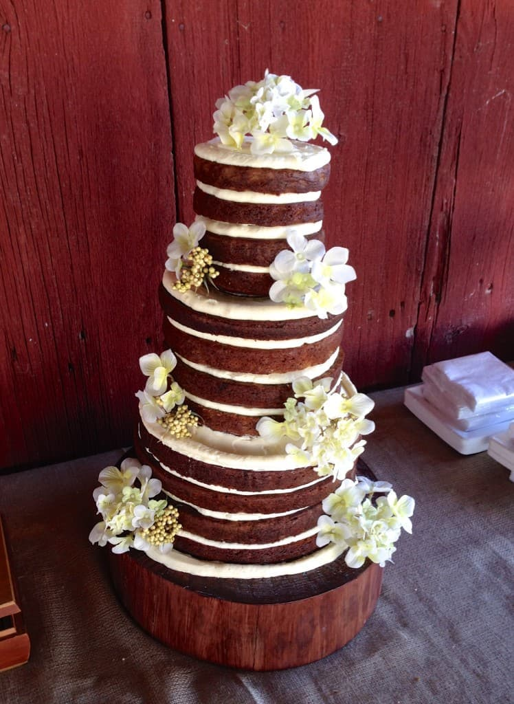 a naked Banana Bread Wedding Cake decorated with flowers