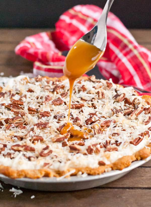 A cream cheese filling is topped with toasted pecans, coconut, and caramel sauce in this incredible pie!