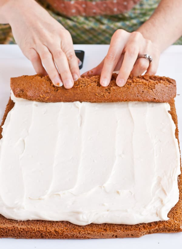 hands rolling pumpkin cake topped with cream cheese filling