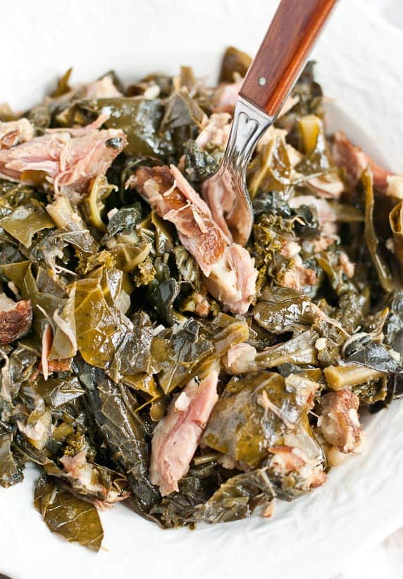 Southern Style Collard Greens with a fork in a white bowl
