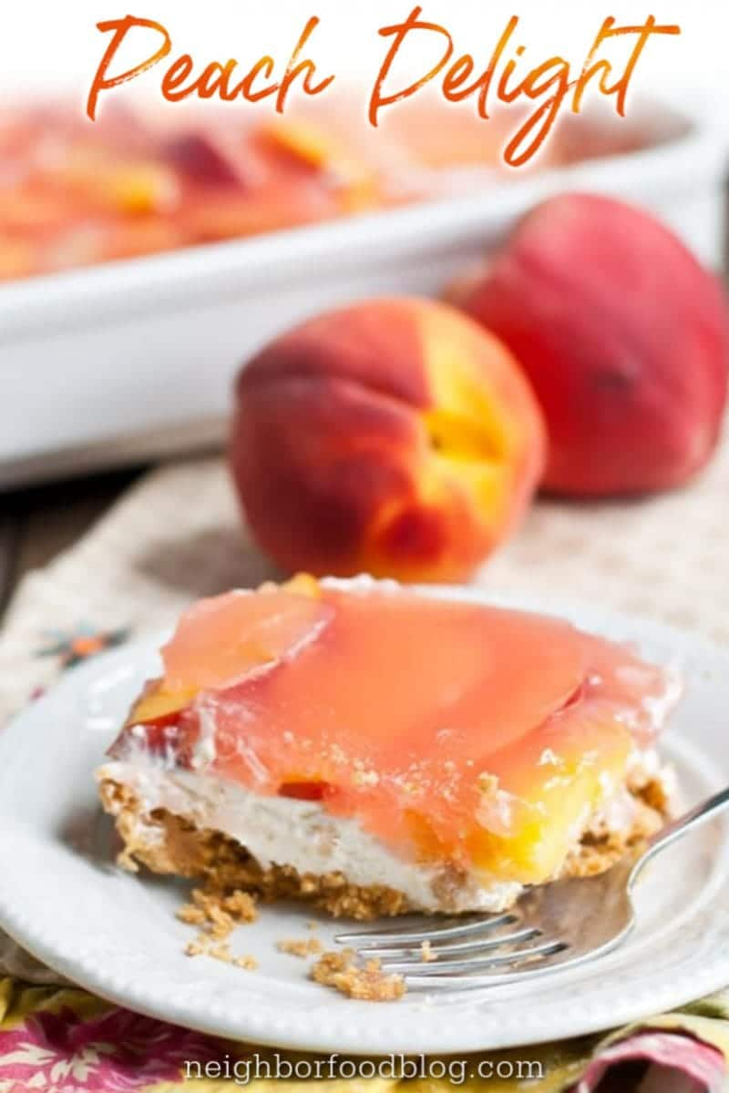 slice of Peach Delight on a plate in front of fresh ripe peaches
