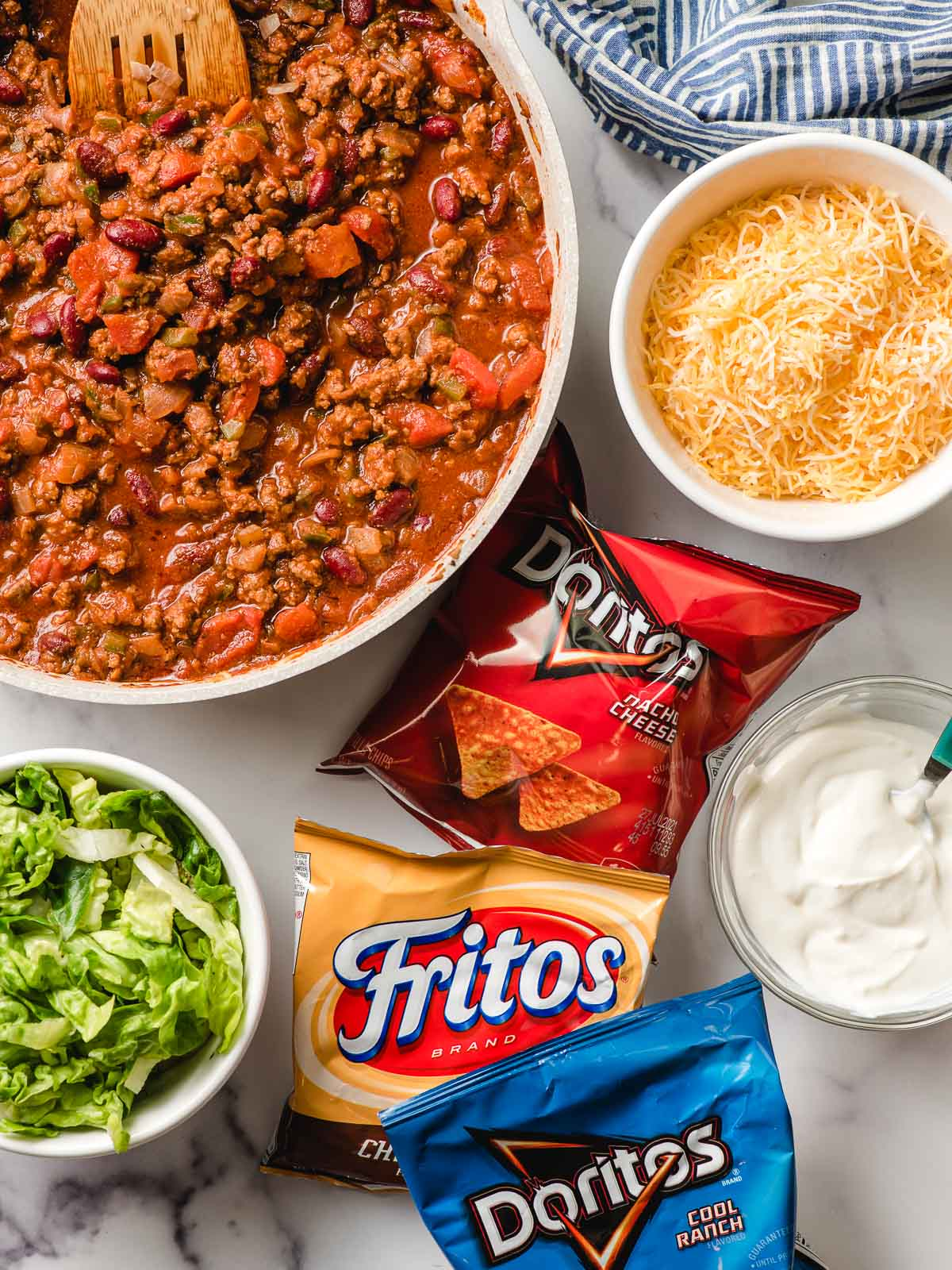 Meat mixture for Walking Tacos with bags of Doritos and Fritos, plus bowls of lettuce, cheese, and sour cream on the side.