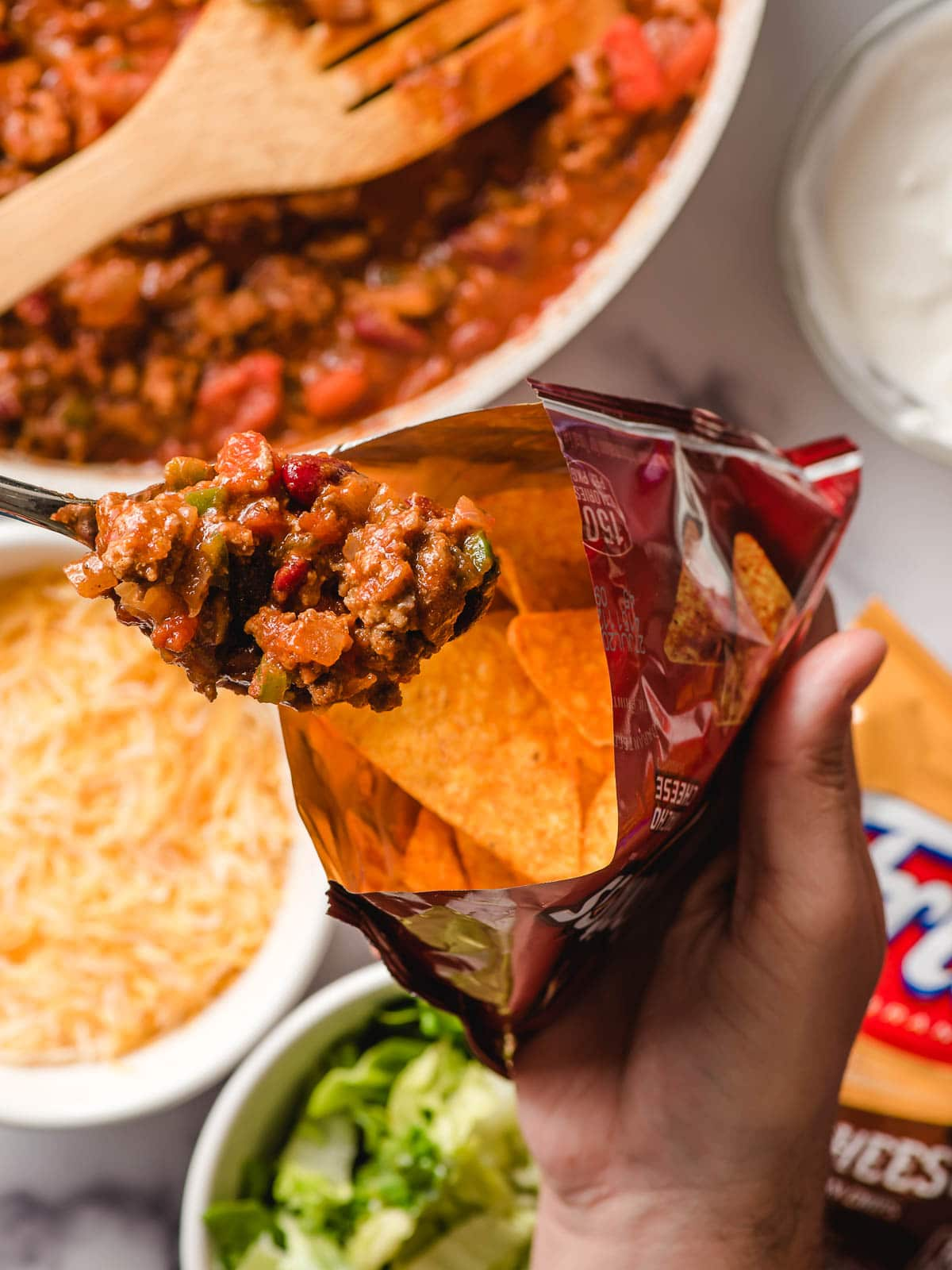 Spoon scooping taco meat into a bag of Doritos.