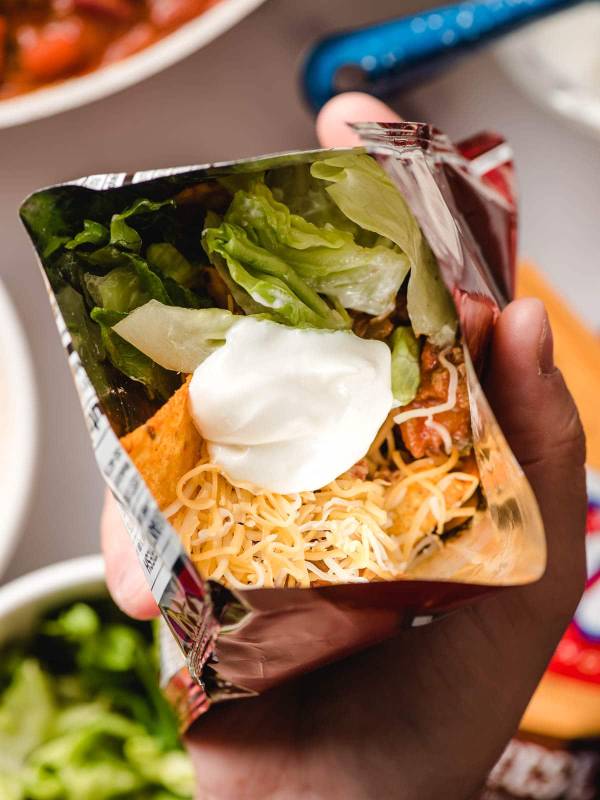 Open bag of chips layered with taco meat, lettuce, sour cream, and cheese.