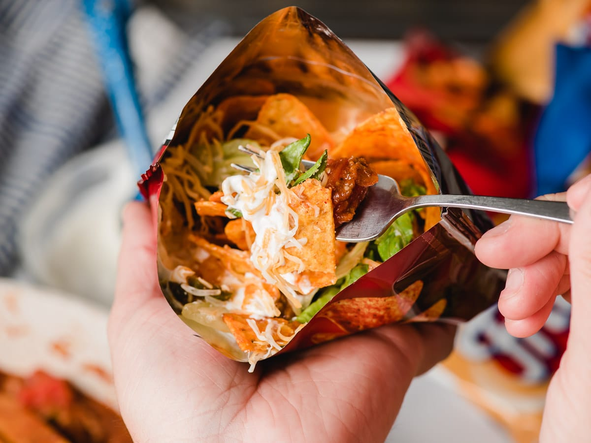 Hand holding bag tacos and another hand taking a bite out of it with a fork.