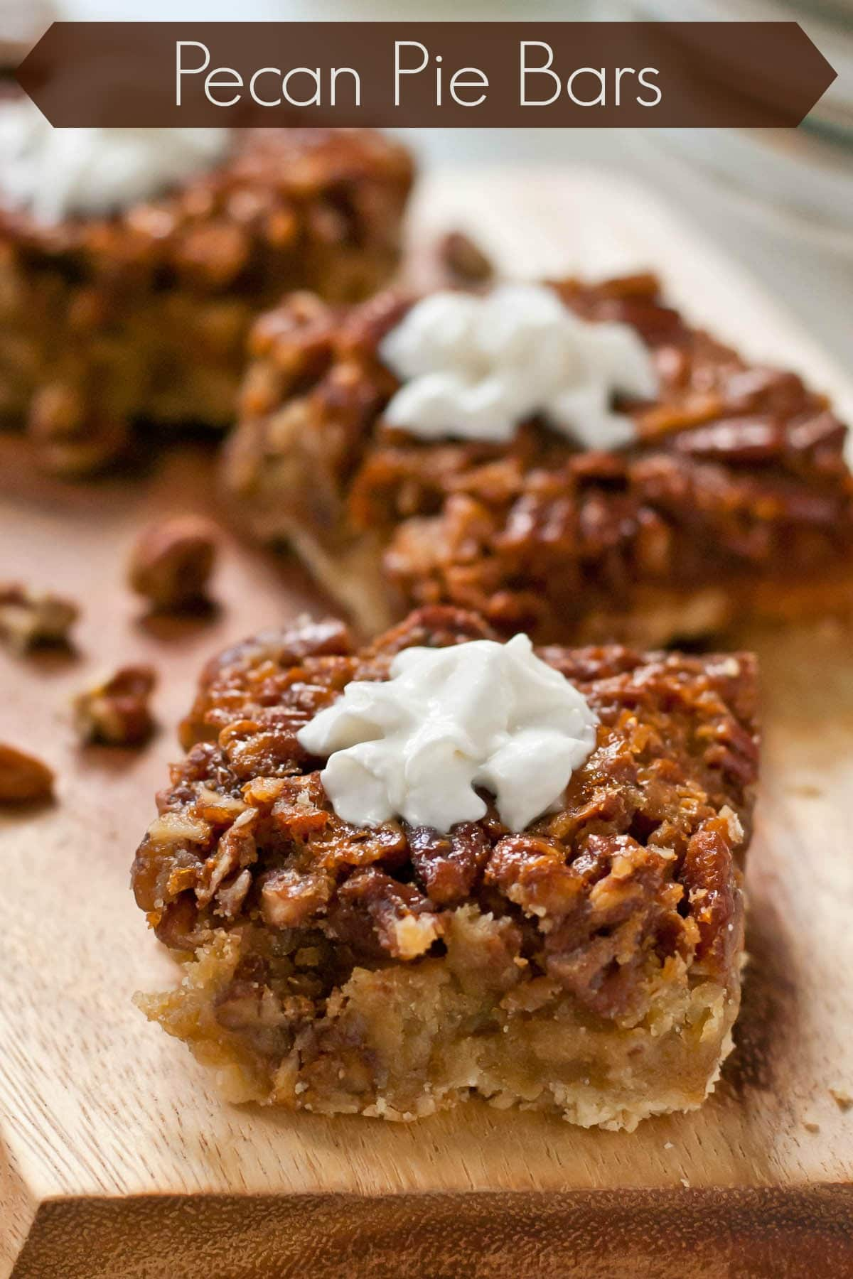 labeled image of several pecan pie bars topped with whipped cream served on a board