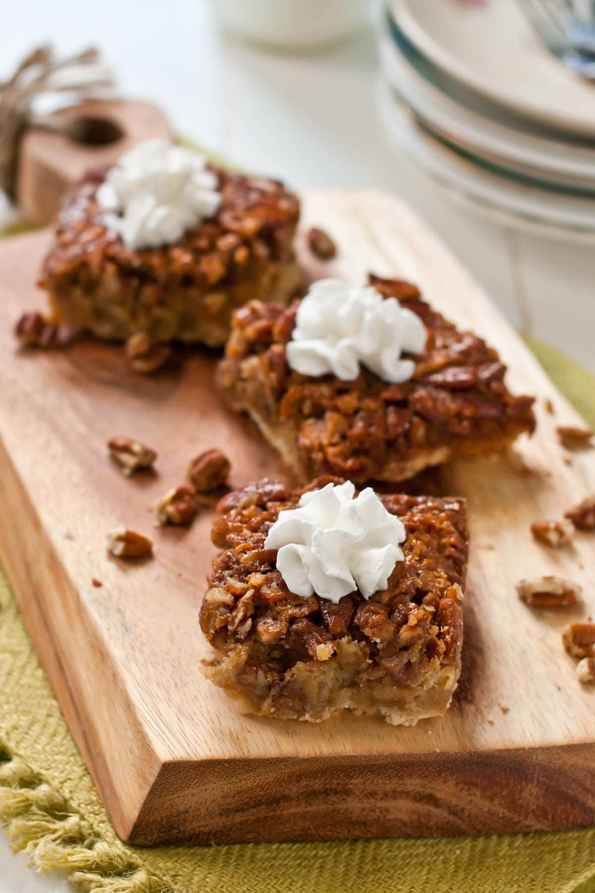 a serving board with pecan pie bars topped with whipped cream