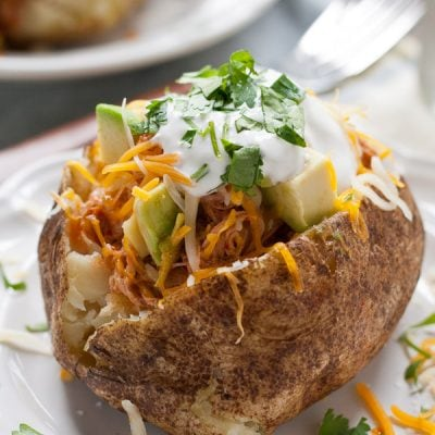 These Chicken Enchilada Baked Potatoes are loaded with saucy shredded chicken, cheese, sour cream, and avocado! A perfect weeknight meal.