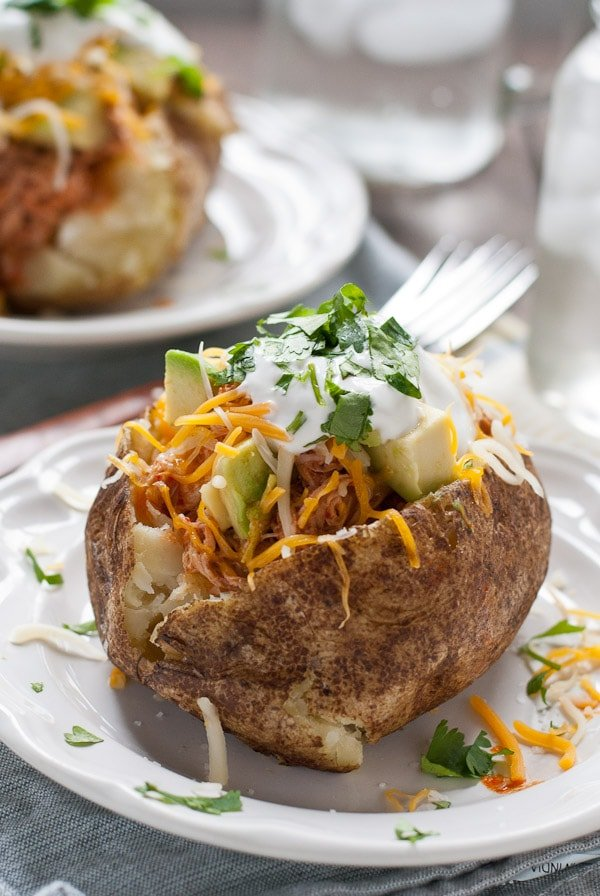 These Chicken Enchilada Loaded Baked Potatoes are an easy and hearty weeknight dinner idea.