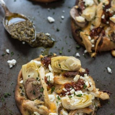 You'll love the combination of flavors in these Naan Pizzas loaded with pesto, chicken, artichoke, feta, and sundried tomato.