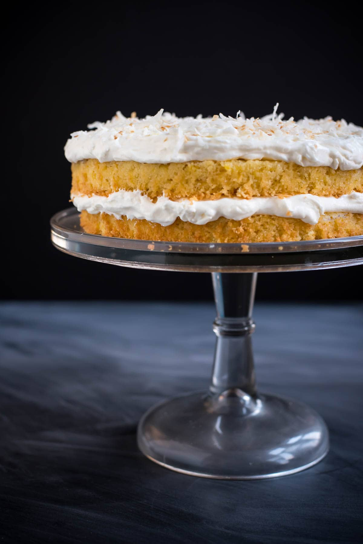Fresh pineapple gives this Pineapple Coconut Cake so much tropical flavor and the fluffy coconut frosting is divine!