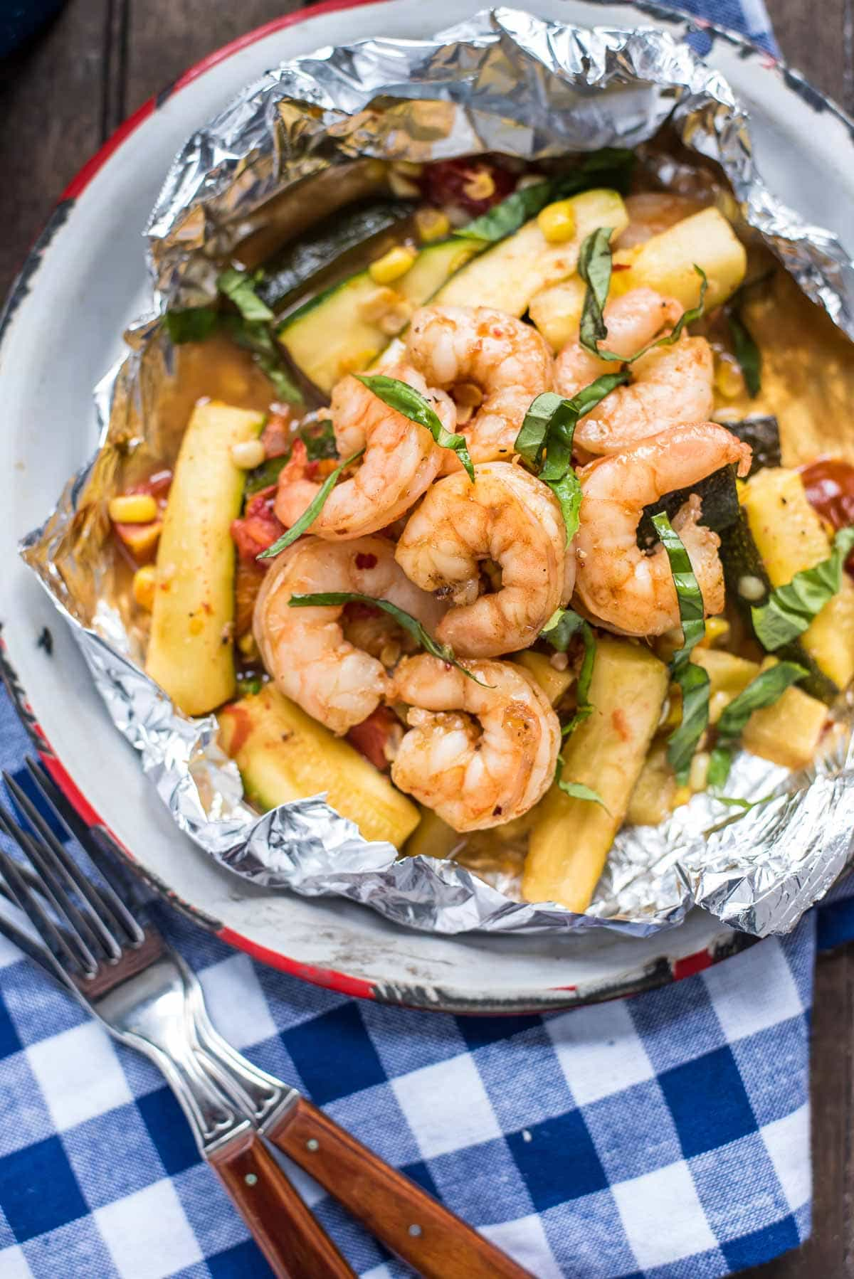 These Honey Garlic Shrimp Foil Packets are loaded with zucchini, corn, and tomatoes in a killer sweet and savory glaze.