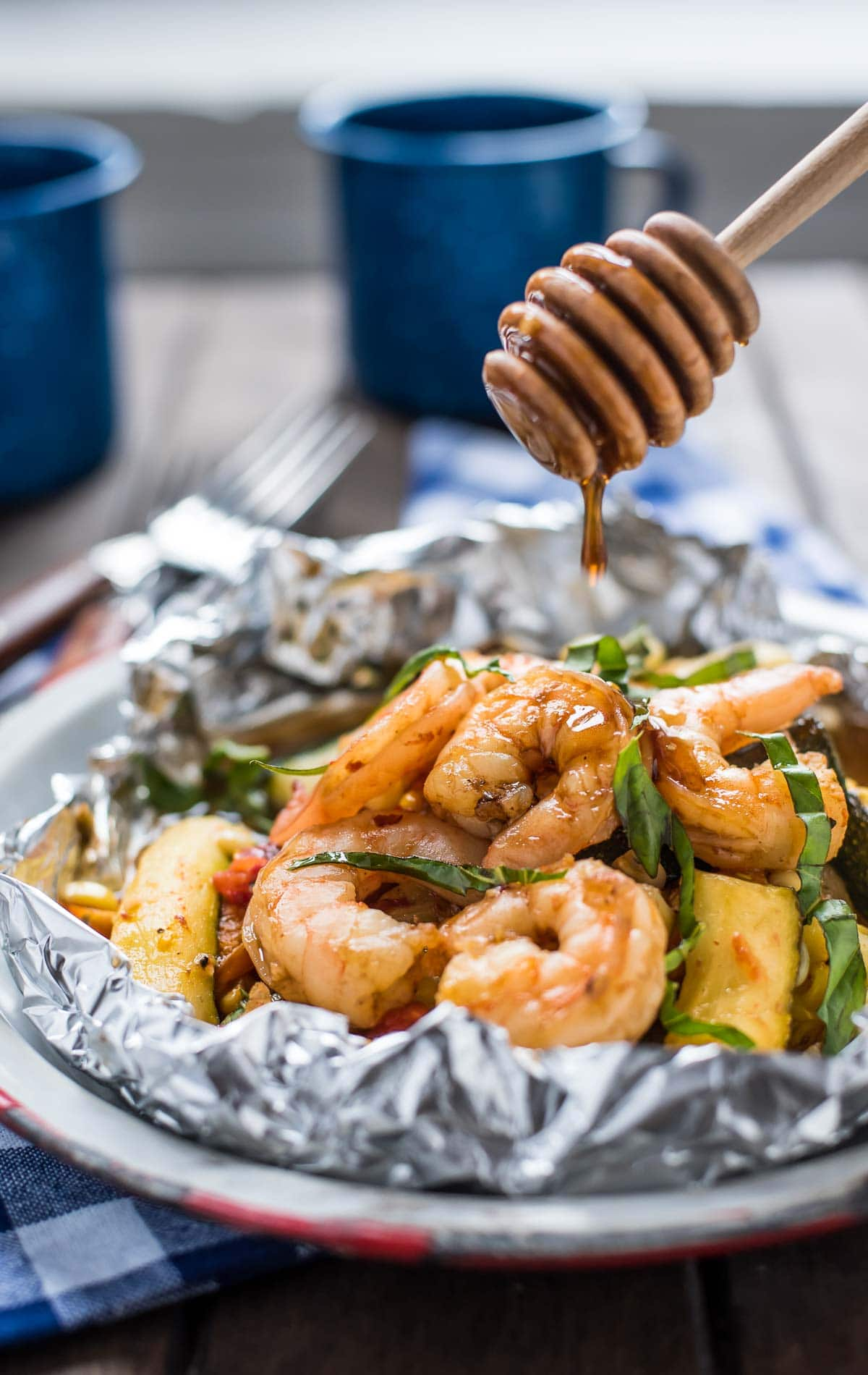 These Honey Garlic Shrimp Foil Packets with zucchini, tomatoes, and corn are the ultimate easy summer meal!