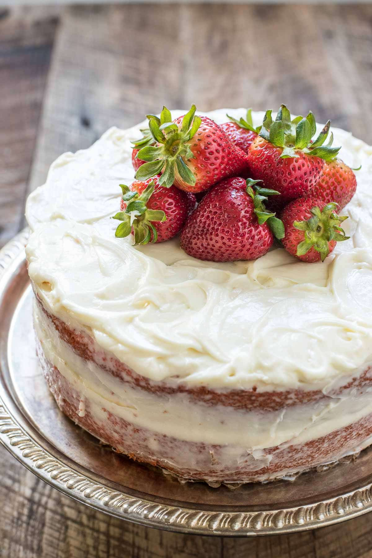 Easy strawberry cake with cream cheese frosting and fresh strawberries on top
