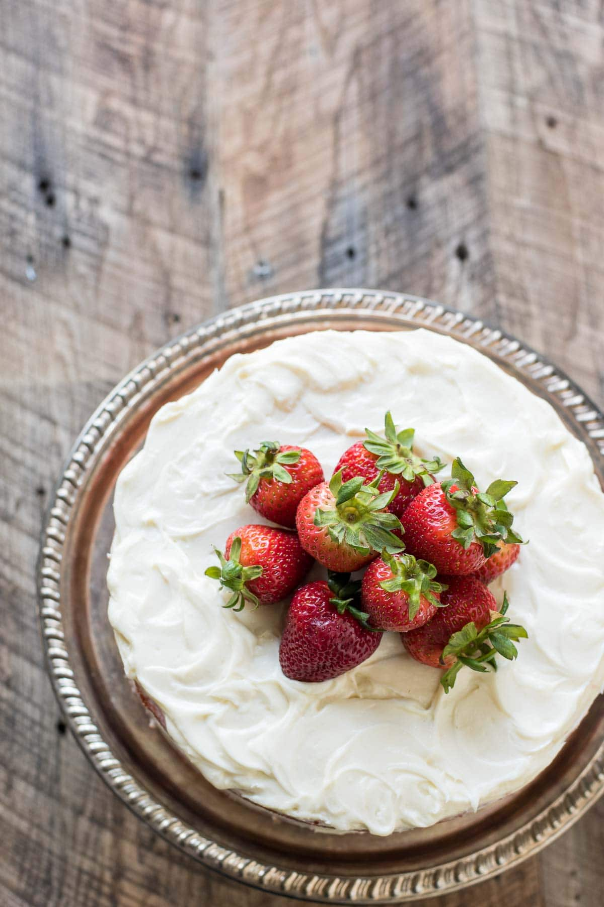 Strawberry cake frosted with cream cheese frosting and fresh strawberries