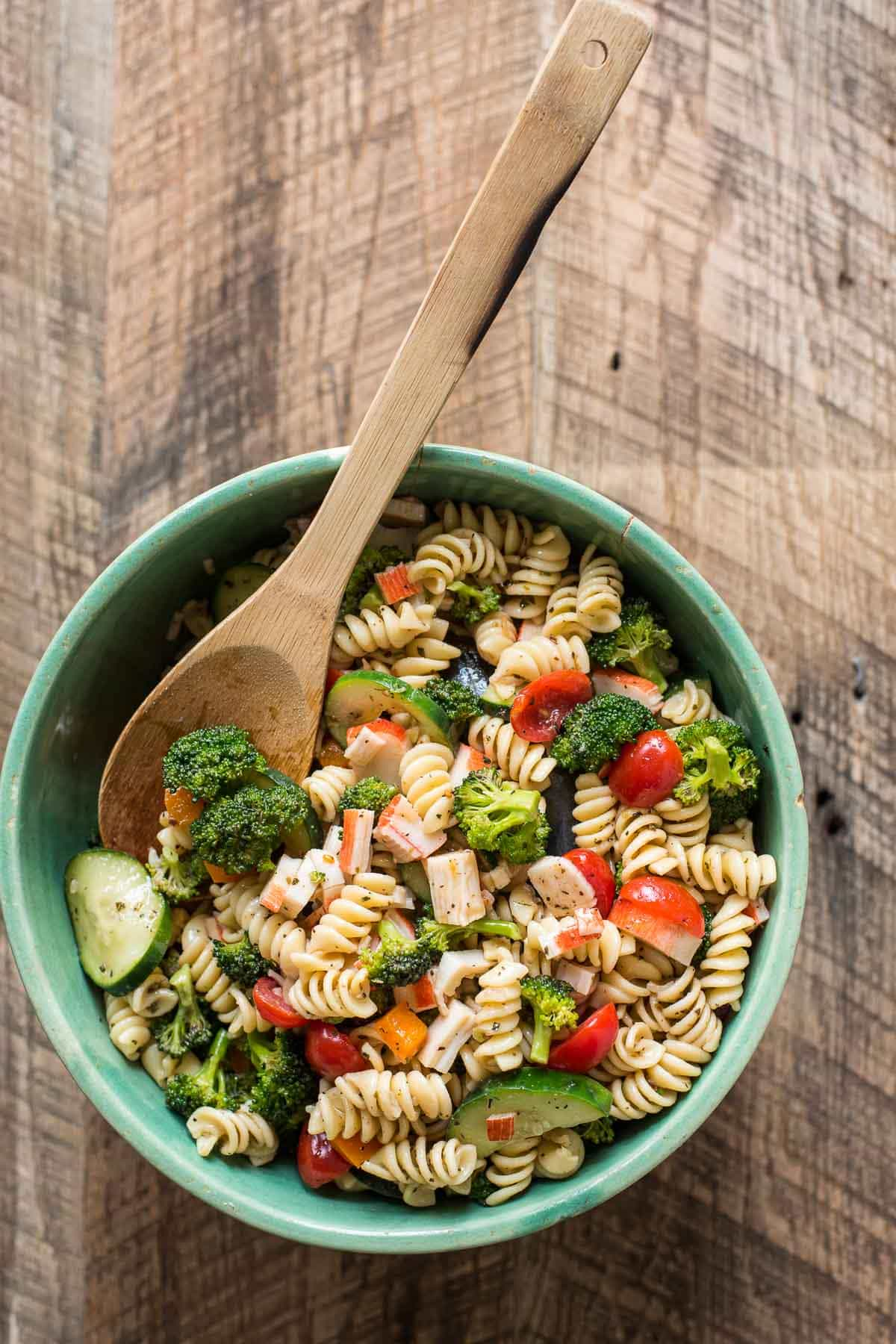 This Greek Pasta Salad with Feta Cheese is loaded with fresh veggies, crab, and a tangy Greek vinaigrette.