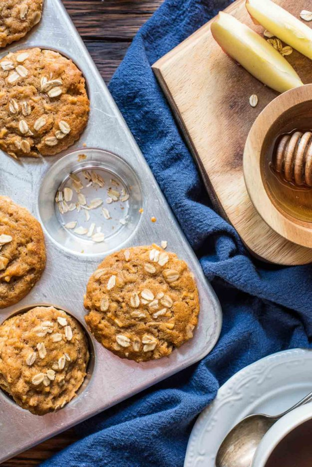 a muffin tin with golden brown muffins sprinkled with oats, a blue napkin and a honey spoon