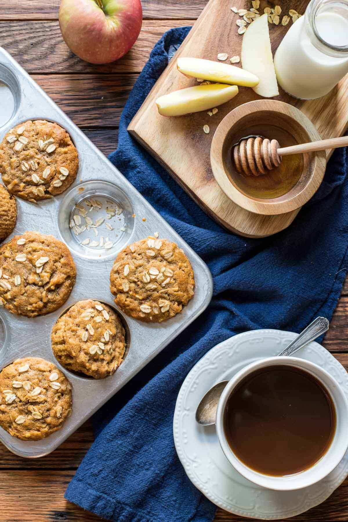 a tin of Apple Cinnamon Muffins beside a cup of coffee, so apples, honey and milk on a table