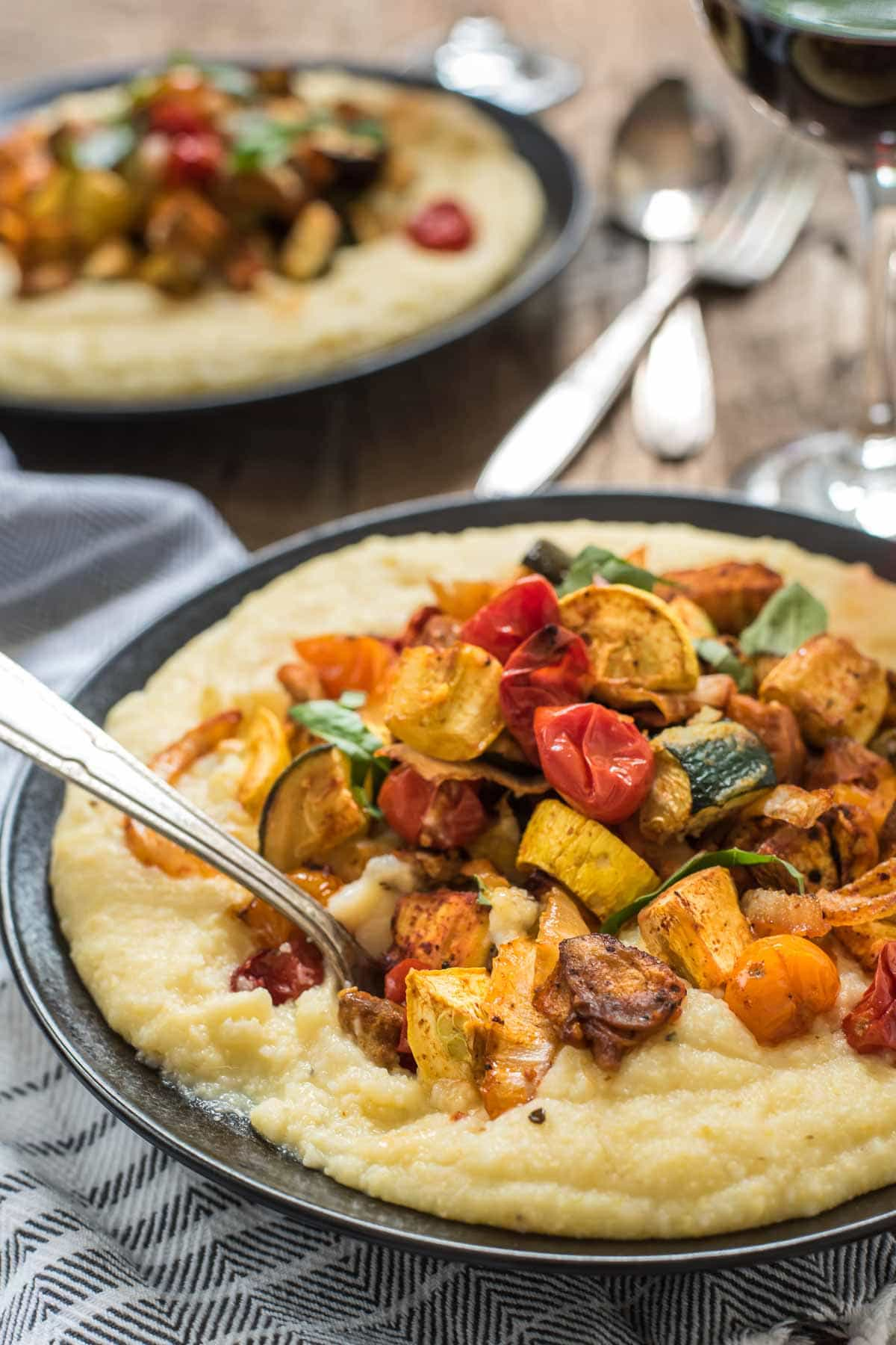 Smoky roasted tomatoes, eggplant, and squash pair beautifully with cheesy polenta in these Roasted Vegetable Polenta Bowls. It's the ultimate late summer comfort food!
