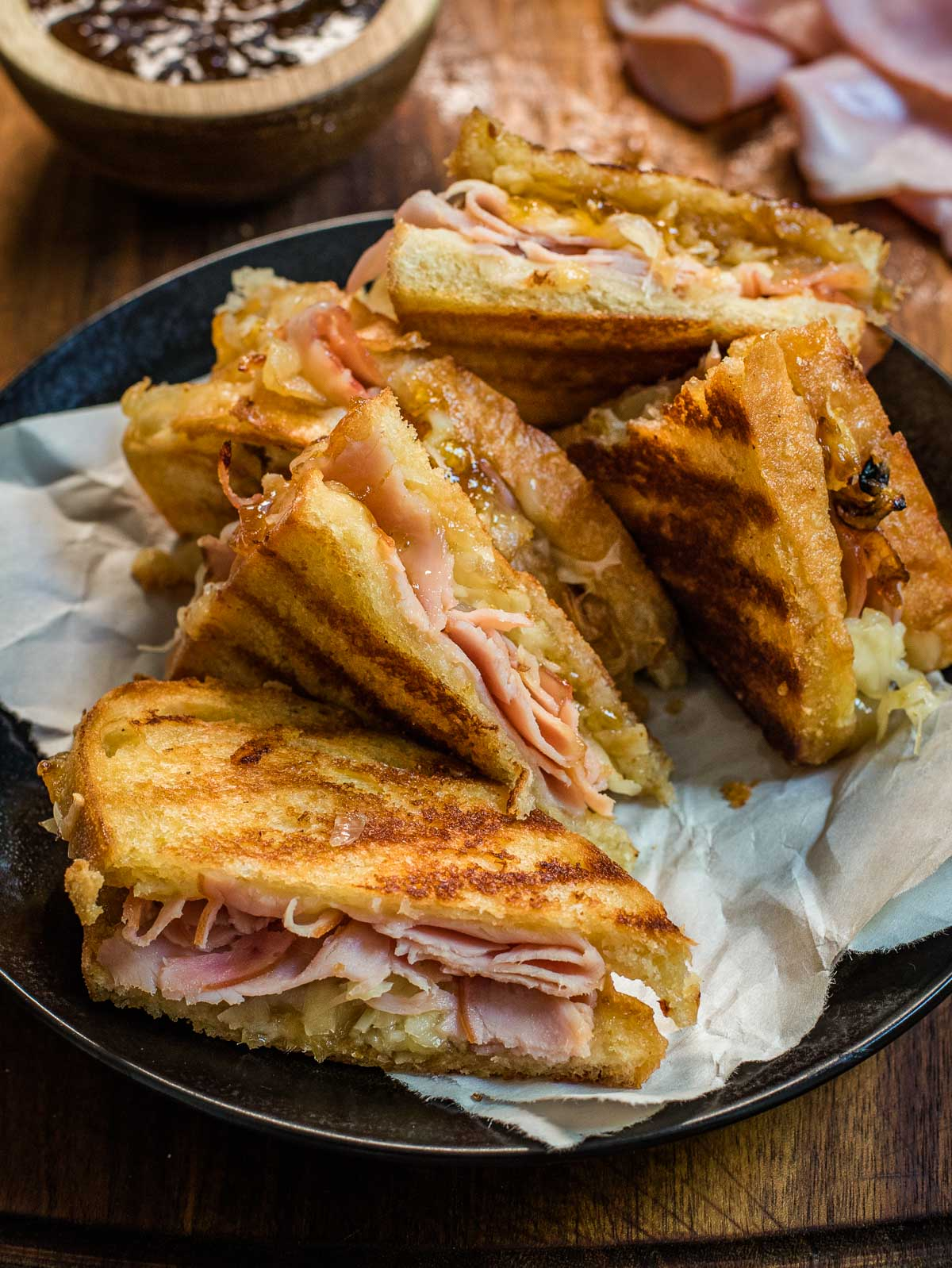 Criss crossed grilled cheese halves ona black plate.