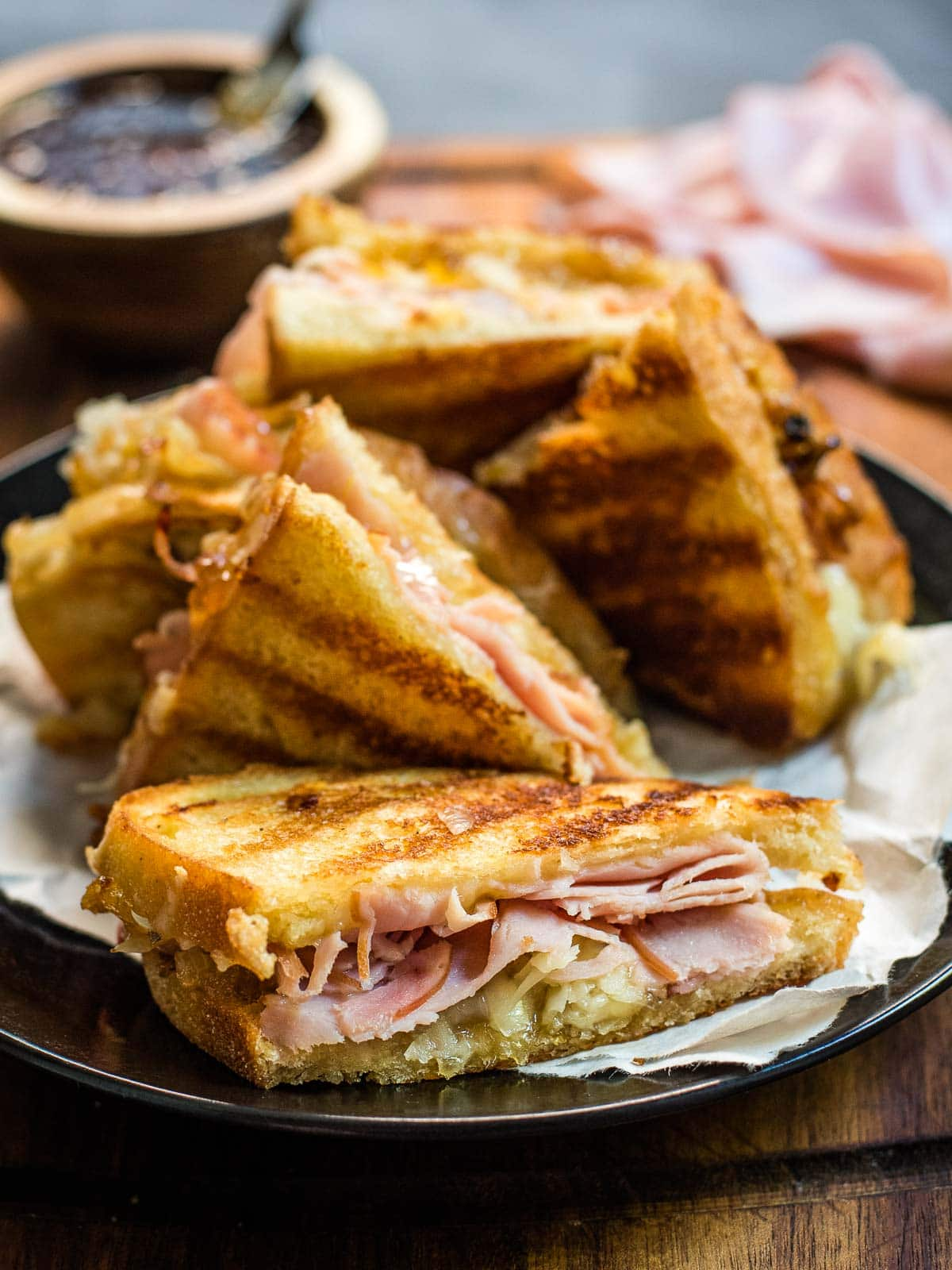 Side view of a Gruyere grilled cheese with ham slices on a black plate.