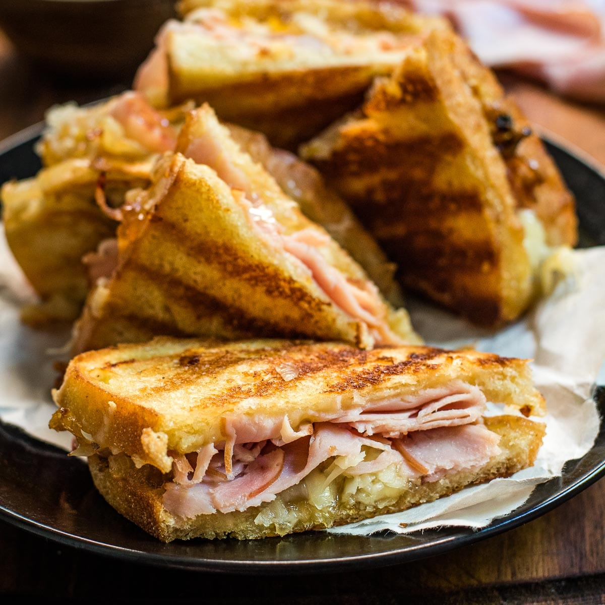 Gruyere grilled cheese sliced in half to reveal the melty cheese, ham slices, and caramelized onions.