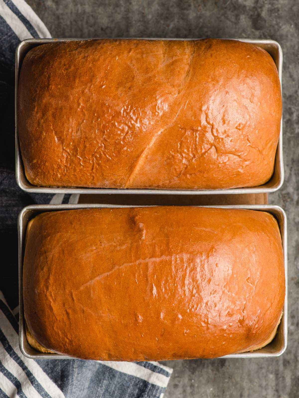 Two loaves of baked Amish white bread side by side.
