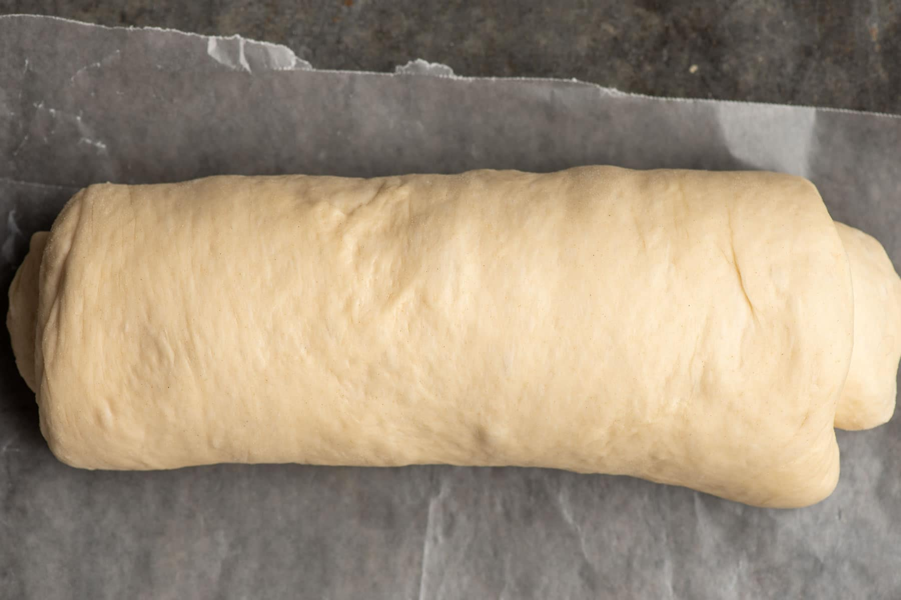 Bread dough rolled up on a piece of parchment paper.