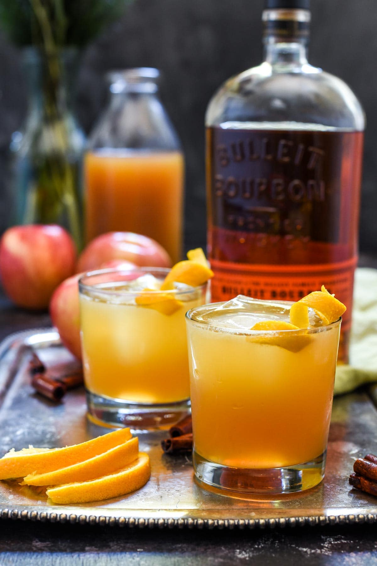 Two apple cider cocktails sit on a serving tray with drink ingredients around