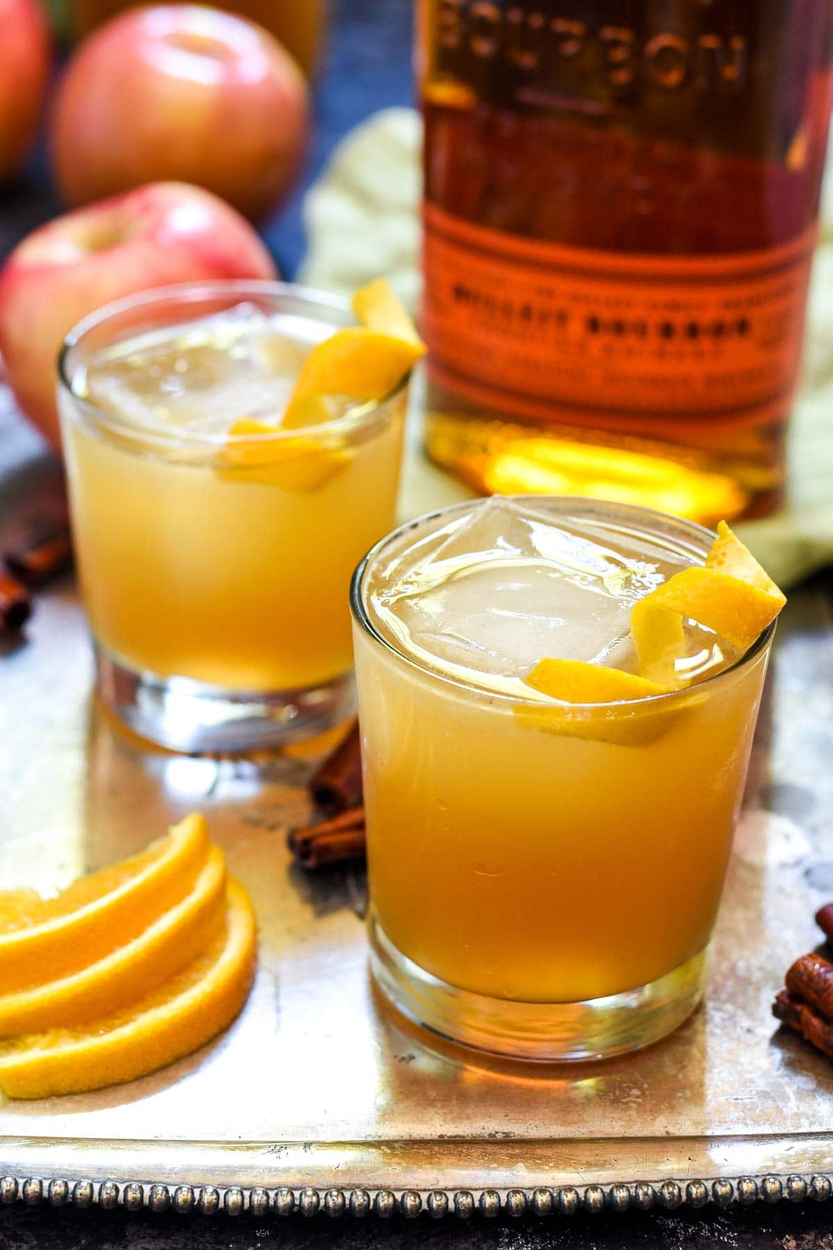 Two apple cider cocktails with ice and orange peel on a serving tray