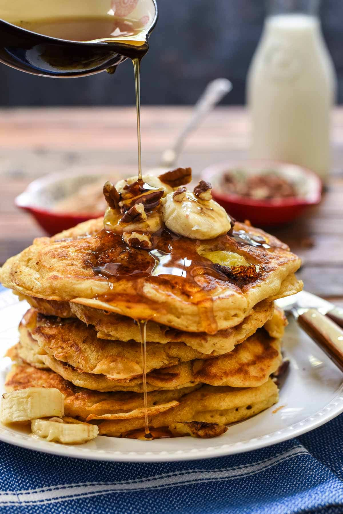 a stack of banana nut pancakes being drizzled with syrup