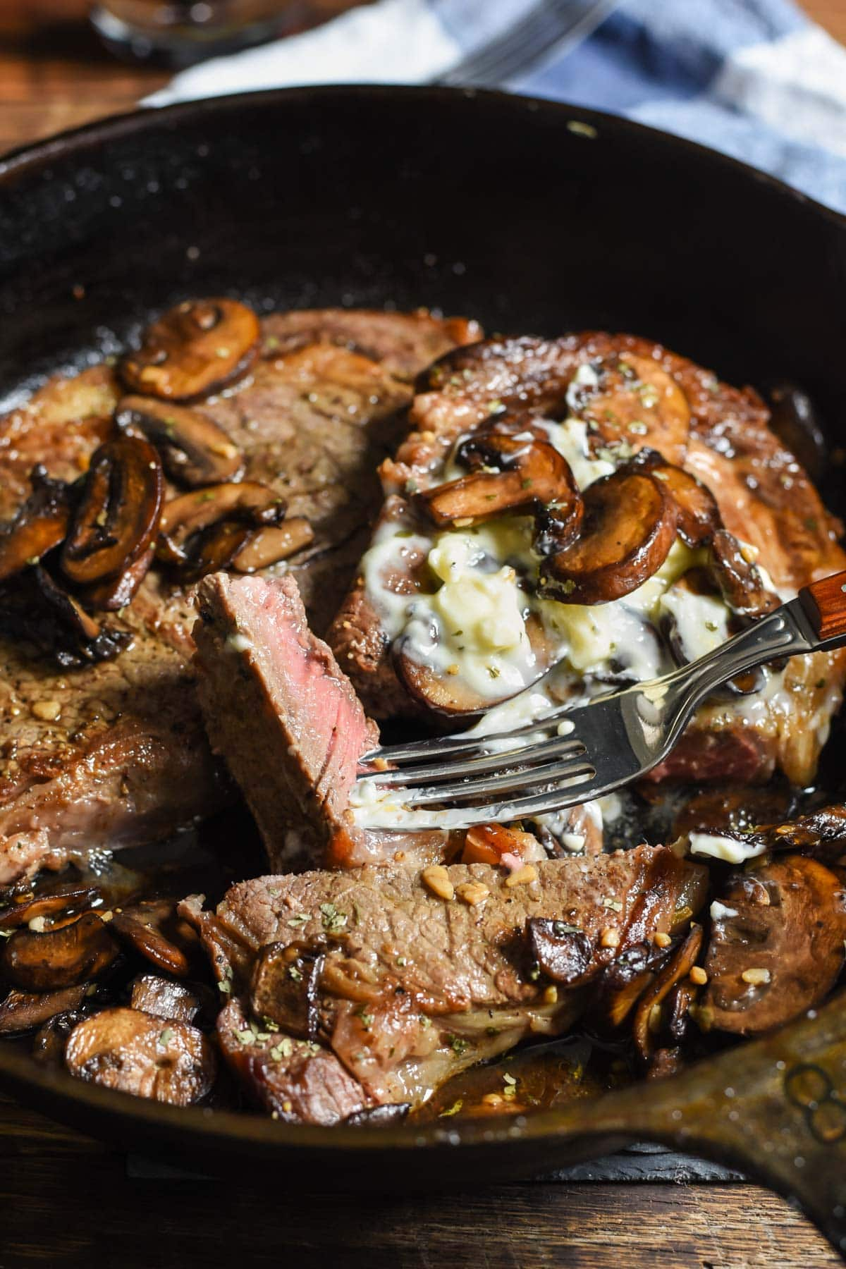 a bite of juicy pink ribeye steak surrounded by garlic mushrooms and butter in a cast iron skillet