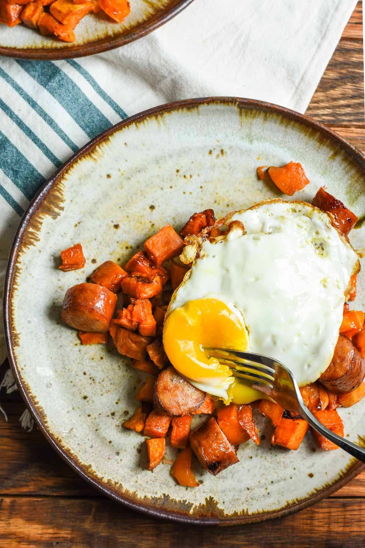 A fried egg completes this Maple Roasted Sweet Potato Sausage Hash--an easy weeknight dinner or breakfast idea!