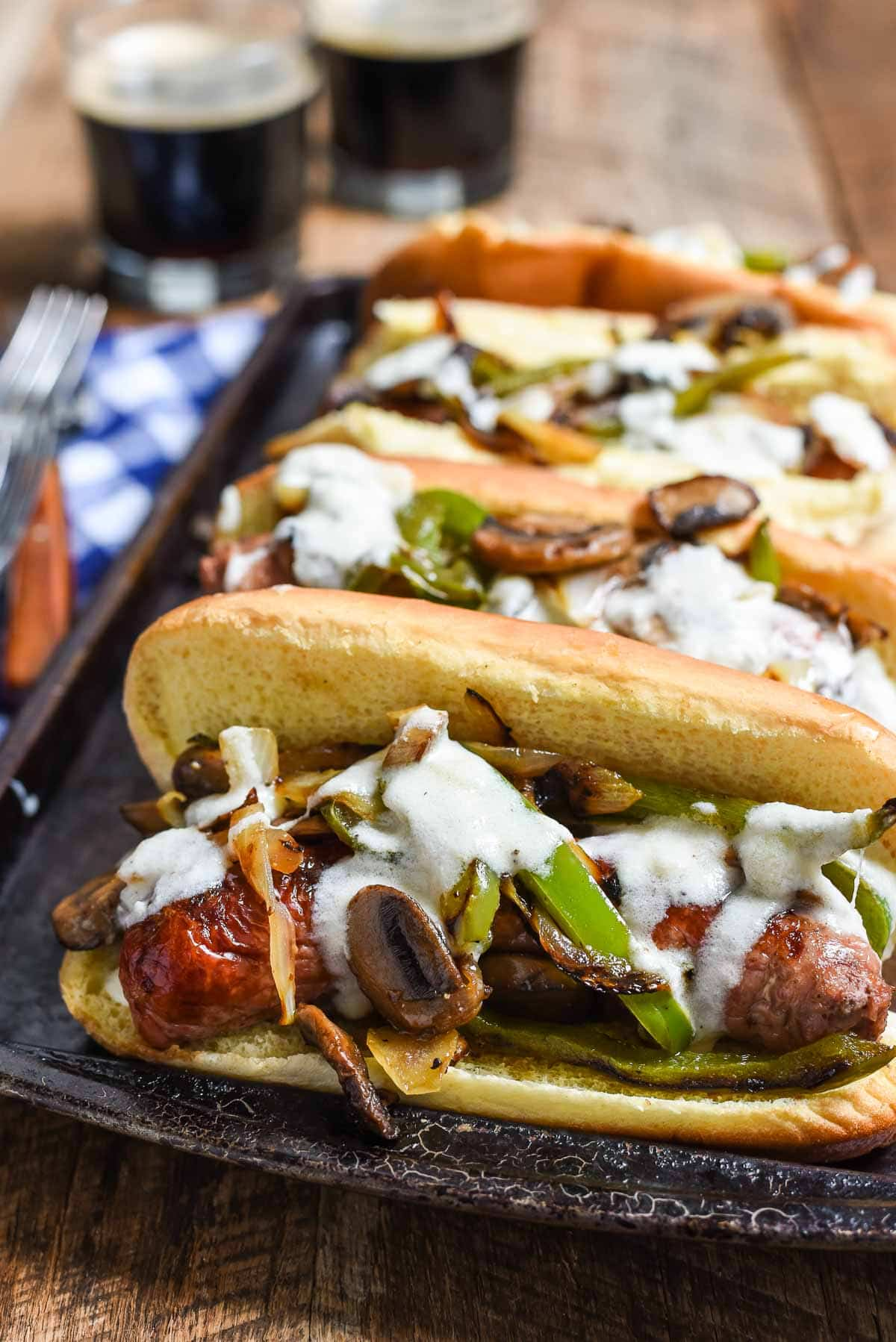 Philly Cheese Brats are a quick 30 minute meal perfect for grilling! Juicy brats with bell peppers, onions, mushrooms, and a creamy cheese sauce!