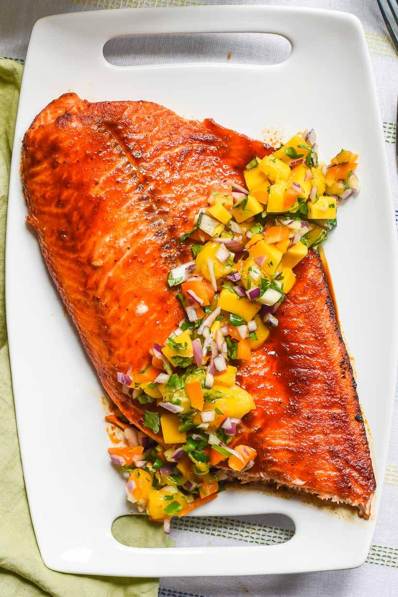 white platter with large salmon filet with mango salsa
