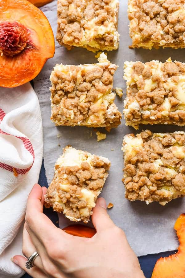 Peach Cobbler Cheesecake Bars combine two of my favorite desserts for an awesome summer treat.