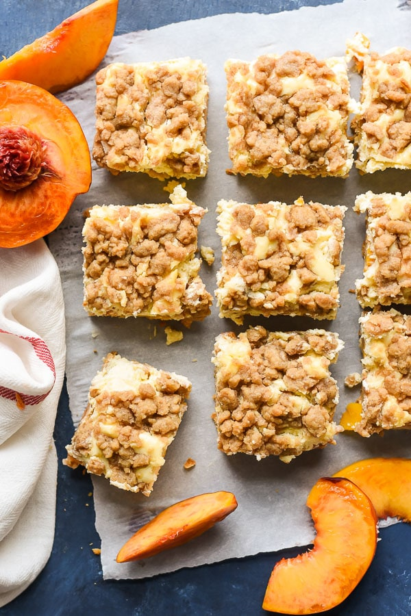 These Peach Cobbler Cheesecake Bars combine the brown sugary crunch of peach cobbler with the creaminess of cheesecake for the ultimate summer dessert.