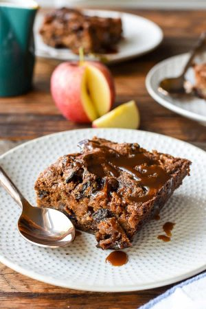 This Spiced Apple Cake is loaded with dried and fresh fruit and covered in bourbon caramel sauce for an irresistible fall dessert!
