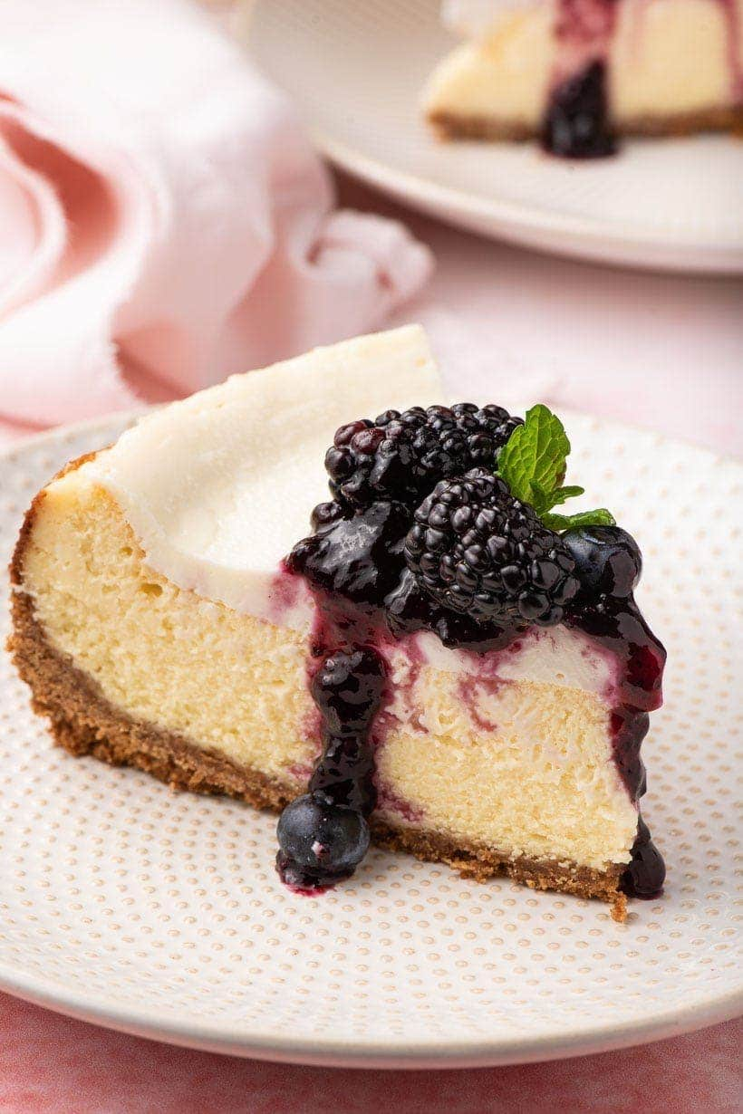 cheesecake slice with sour cream topping and blueberry preserves