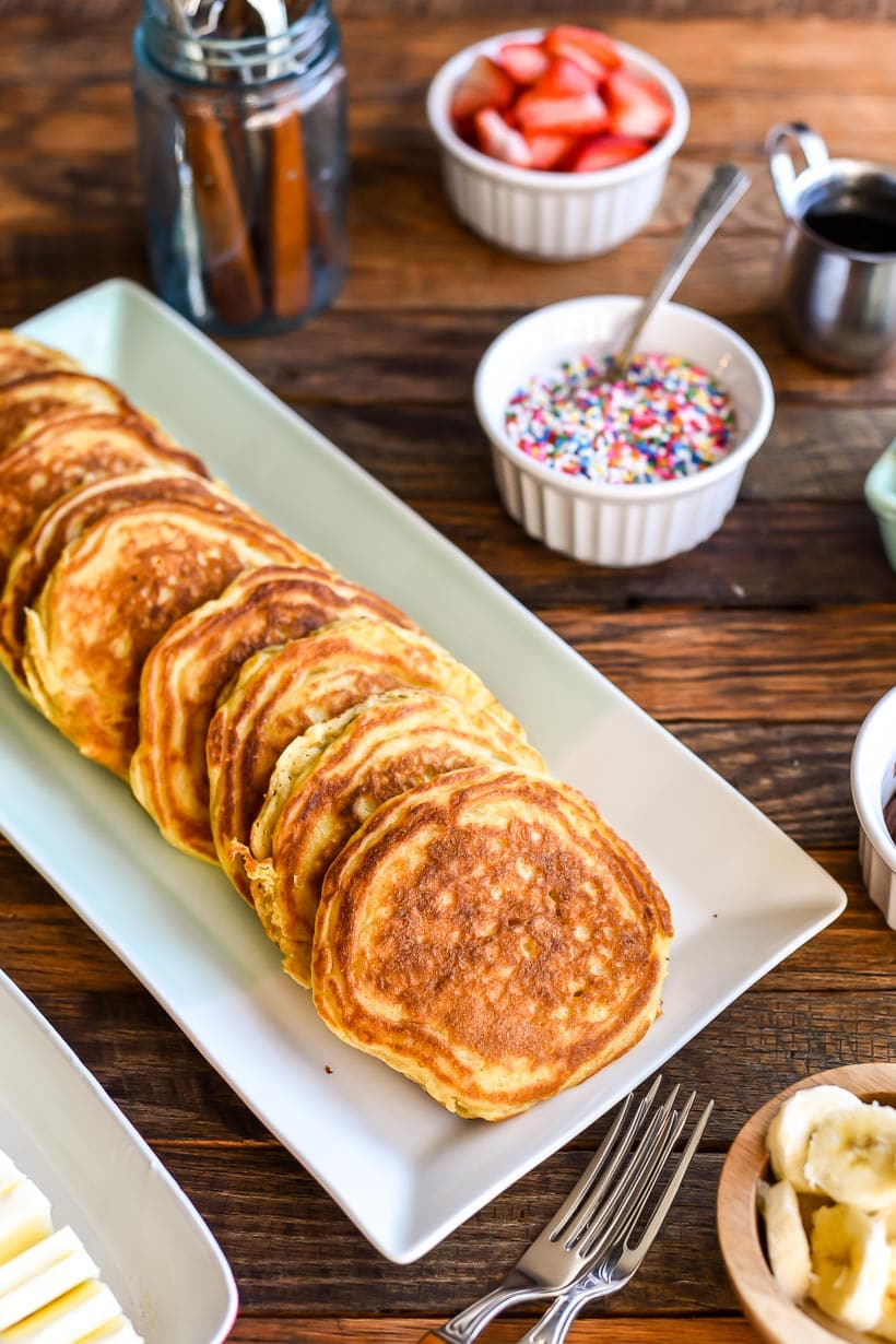 Pancakes lined up on a platter with bowls of sprinkles, strawberry slices, and banana slices in the background.