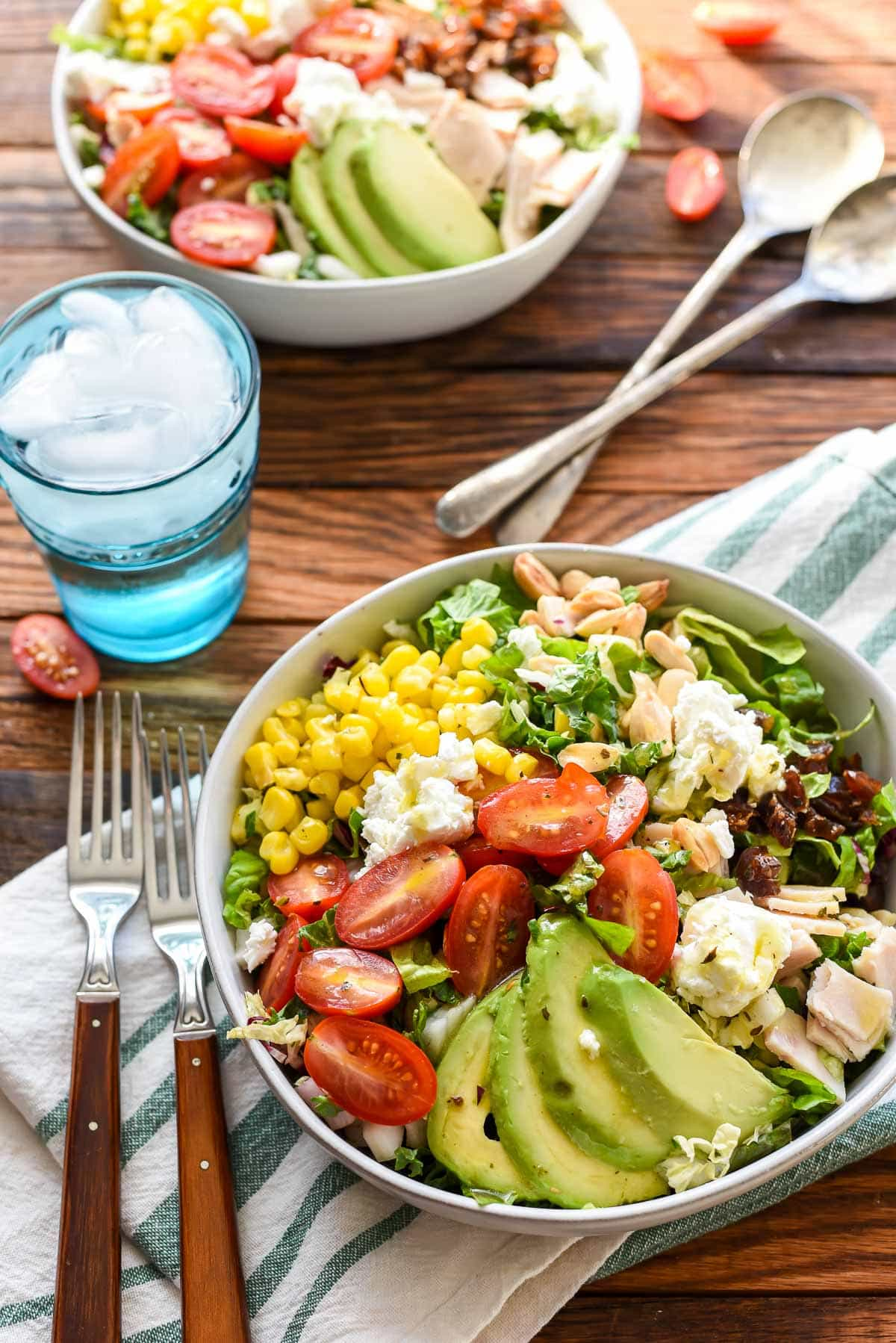 This Chopped Salad is loaded with avocado, dates, goat cheese, corn, and tomatoes for a filling, flavor packed meal!