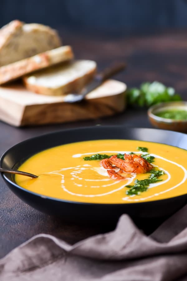 Roasted Butternut Squash Soup with a drizzle of coconut milk, herb sauce, and shrimp on top
