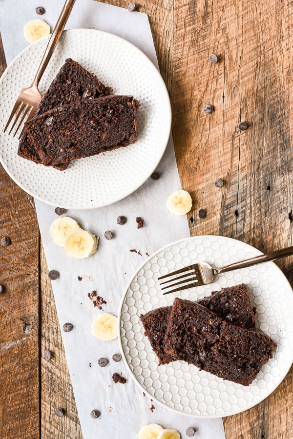 Two plates with slices of chocolate banana bread on them