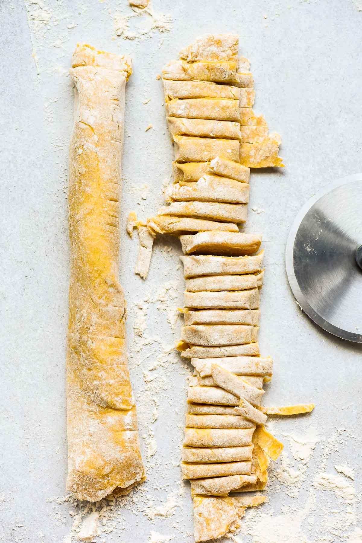 Homemade Egg noodle dough rolled up and cut into strips
