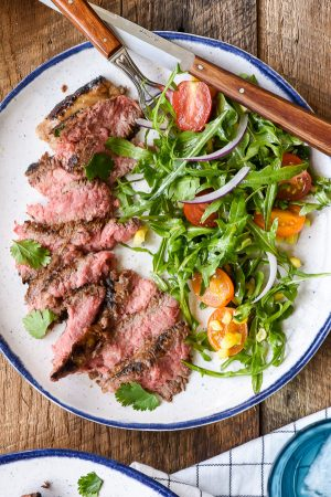 Sliced Marinated Skirt Steak on a plate with summer salad