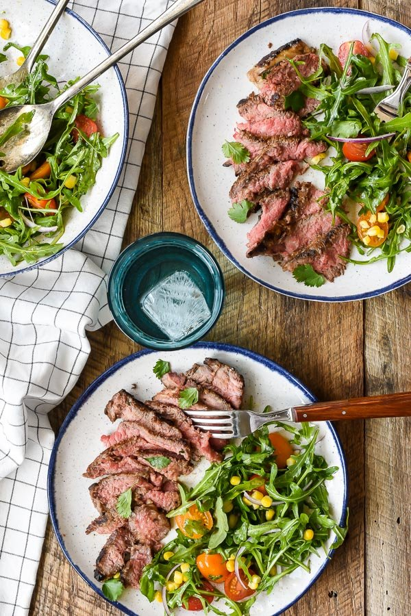 2 plates with marinated skirt steak and summer salad