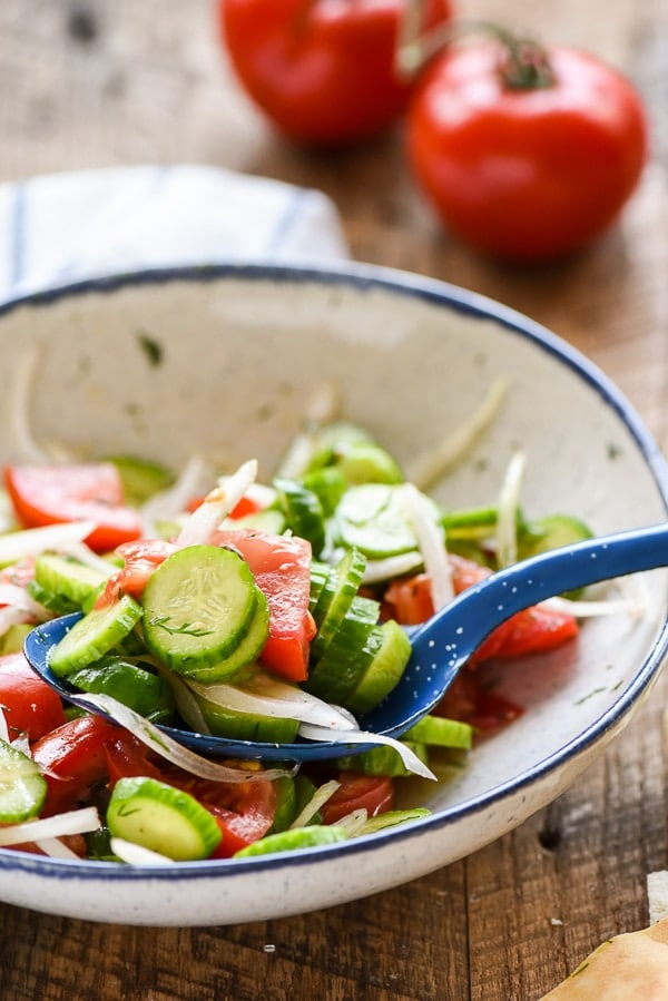 Cucumber and tomato salad scooped with spoon